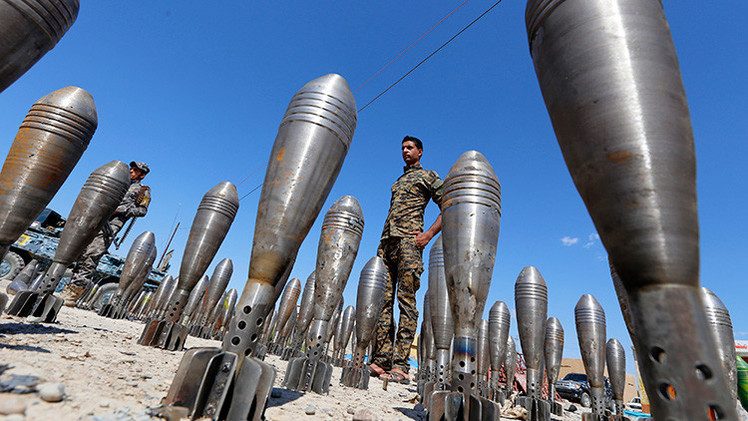 Un miembro de las fuerzas de seguridad iraquíes está entre municiones incautadas del Estado Islámico
