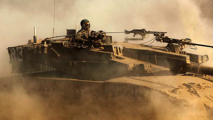Un soldado israelí se desplaza en un tanque cerca de la frontera con Gaza