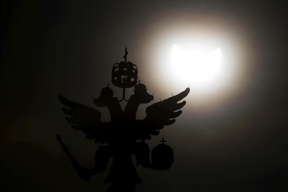 Silueta del águila bicéfala sobre el Museo Estatal de Historia con el eclipse solar de fondo. Moscú