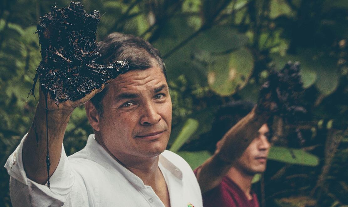 Ecuador's President Rafael Correa raises an oil-coated hand