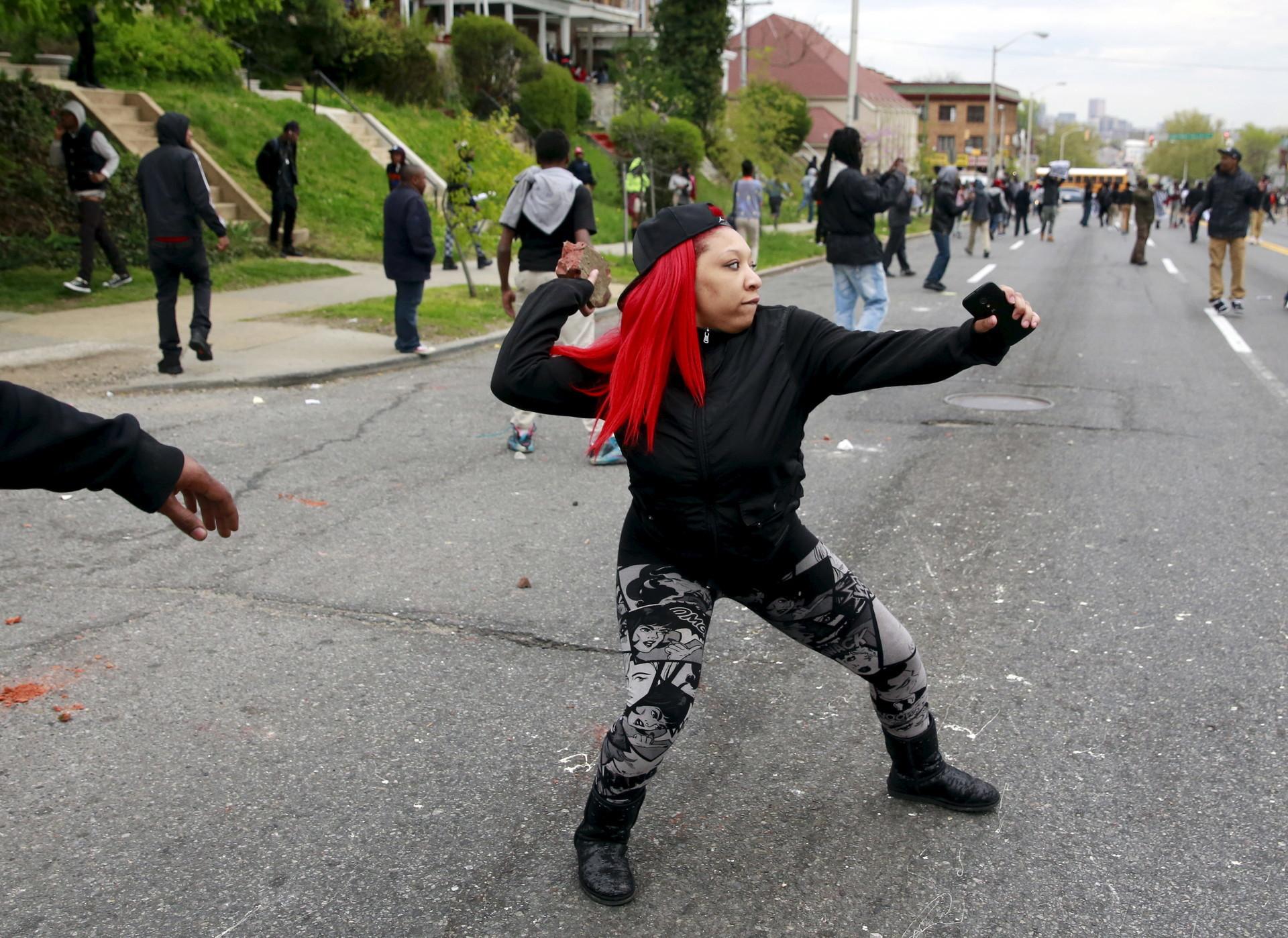 Mujer lanza piedras durante la protesta