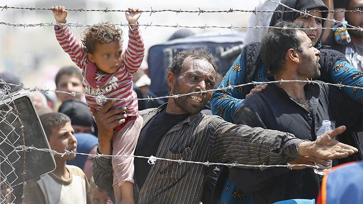 Foto conmovedora: Una niña siria y su padre huyen desesperados del Estado Islámico