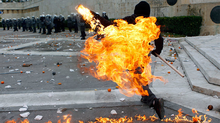 Un manifestante lanza una bomba incendiaria. 6 de diciembre de 2011.