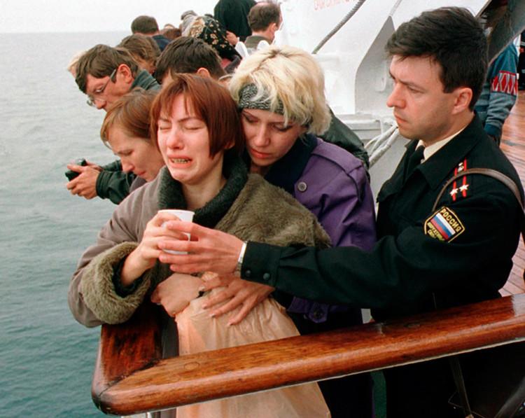 Un oficial de marina ofrece una bebida a una familiar de un marinero fallecido en la tragedia del Kursk durante una ceremonia celebrada en el  lugar donde se hundió el submarino.
