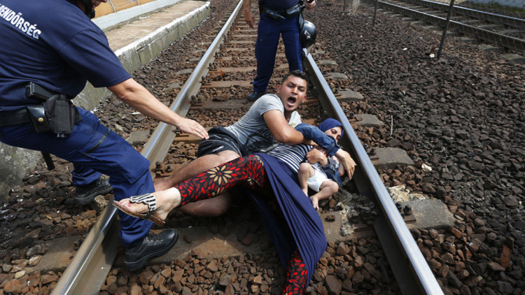 Video: Refugiados sirios se aferran con un bebé a las vías del tren para evitar que los deporten