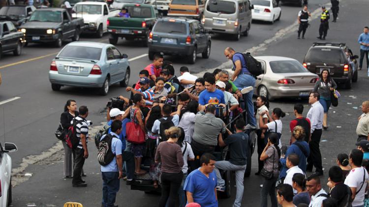 La gente trata de abordar una camioneta en Mejicanos, El Salvador.