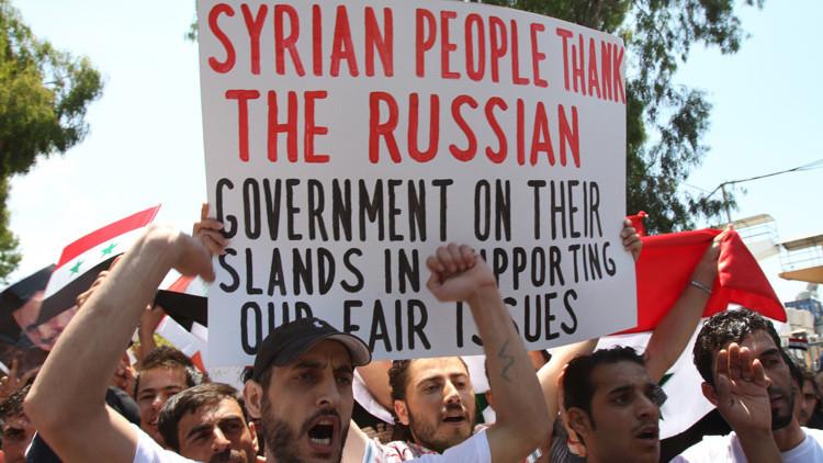 Manifestantes libaneses y sirios ondean banderas sirias y un cartel agradeciendo a Rusia por apoyar al presidente Bashar al Assad.