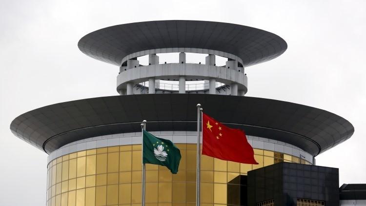 Una bandera de china (D) y una de Macao ondean delante del Sands Macao en Macao, China