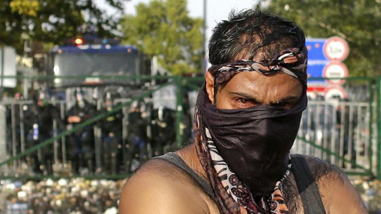 Un refugiado frente a la policía antidisturbios de Hungría en el cruce fronterizo con Serbia