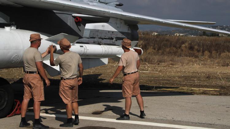 Los militares rusos cargan un misil en la lanzadera del avión de combate Sukhoi Su-24 en la base aérea de Jmeimim en Siria.