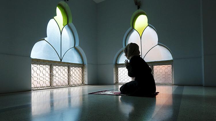 Una mujer reza en una mezquita