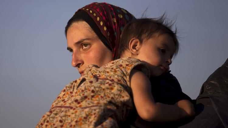 Una mujer siria lleva a su hijo en brazos
