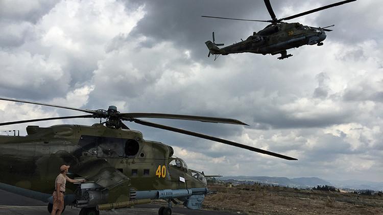 Un técnico al lado de helicóptero de ataque ruso Mi-24 en la base de Jmeimim