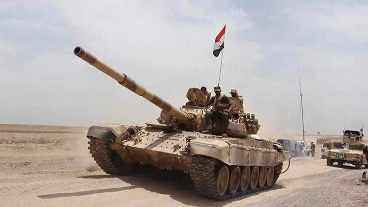 Paramilitares chiitas y soldados del Ejército iraquí viajan en un carro de combate desde el lago Tharthar hacia Ramadi (Irak)