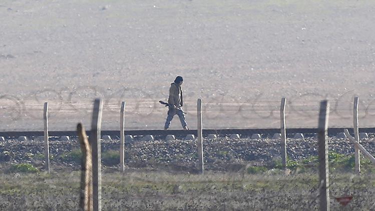 Un hombre armado, supuestamente un militante del Estado Islámico, está cerca de la norteña ciudad siria de Tal Abyad. La foto fue captada desde la ciudad fronteriza turca de Akcakale (sureste de la provincia de Sanliurfa)