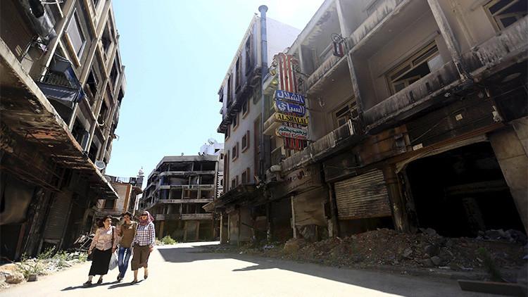 Mujeres caminan en un barrio afectado por los combates de la antigua ciudad de Homs en junio de 2015.