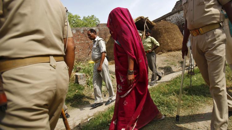 La madre de una de las dos adolescentes que fueron violadas y colgadas de un árbol camina junto con agentes de Policía en el distrito de Budaun, en el Estado indio de Uttar Pradesh.