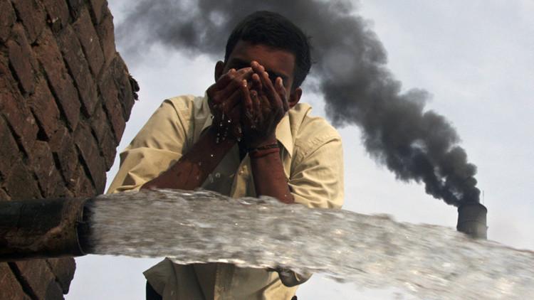 Un trabajador bebe agua junto a una fábrica de ladrillos  cerca de la ciudad india de Chandigarh el 6 de diciembre de 2009.
