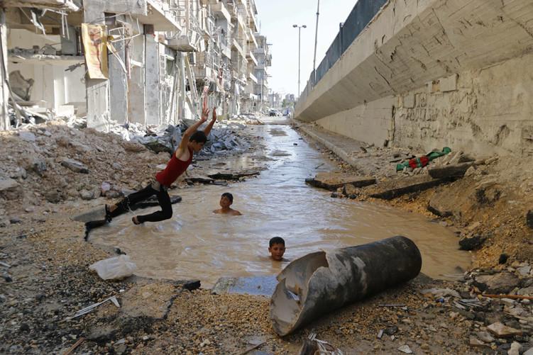 Un niño se sumerge en un 'cráter' lleno de agua en Alepo.