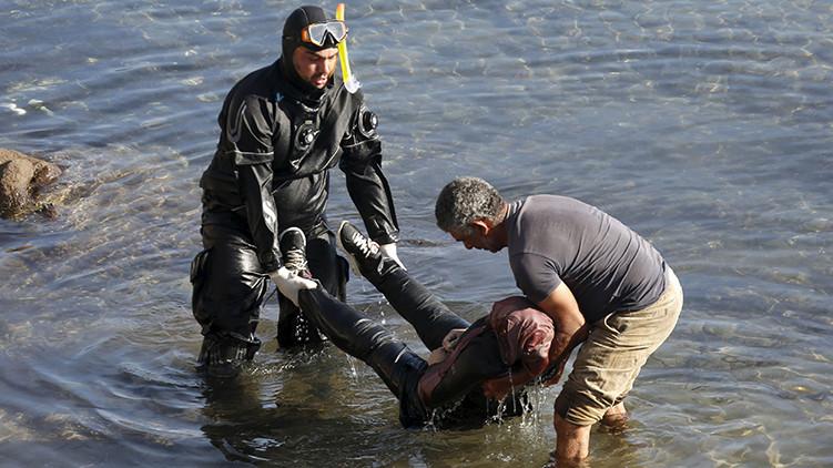 Un hombre ayuda a un guardacostas a trasladar el cuerpo sin vida de una refugiada ahogada en una playa de la isla griega de Lesbos