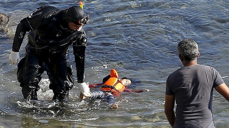 Un guardacostas griego saca el cuerpo inerte de un niño refugiado de una embarcación de madera hundida cerca de la isla griega de Lesbos