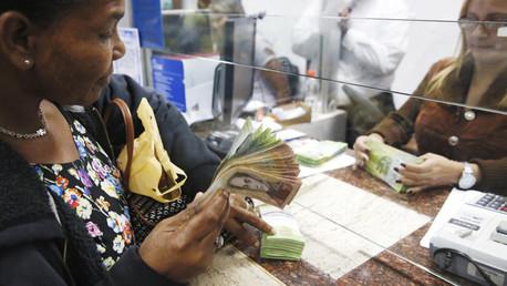 Una mujer cambia dólares por bolívares en Caracas, Venezuela.