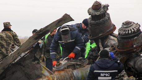 Miembros del equipo del Ministerio de Emergencias de la República Popular de Donetsk examinan un fragmento del tren de aterrizaje del MH17