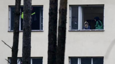Varios refugiados miran a través de la ventana de un centro de detención de extranjeros en Bela-Jezova, República Checa.