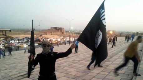 Un combatiente del Estado Islámico sujeta una bandera y un arma en una calle de Mosul, junio de 2014.