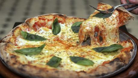 Una pizza Margarita es compartida en una pizzería de San Pablo