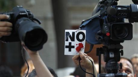Un periodista muestra un cartel de 'No más sangre' durante una protesta contra el asesinato de un trabajador de prensa