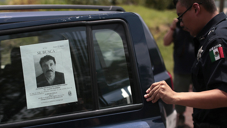 Un agente de la Policía Federeal de México abre la puerta de un auto policial en la que se ve un cartel con la foto del fugitivo capo narcotraficante 'El Chapo' Guzmán.