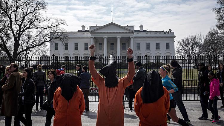Manifestantes vestidos como prisioneros de Guantánamo protestan contra la guerra en el 12.º aniversario de la invasión estadounidense de Irak.