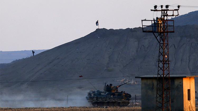 Un blindado del Ejército turco pasa junto a un cerro en la ciudad siria de Kobani, sobre el que ondea una bandera del Estado Islámico, octubre de 2014.