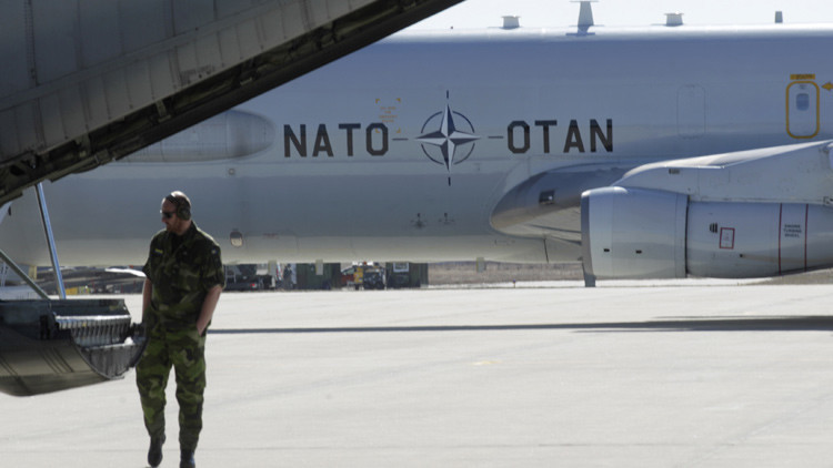 Un especialista militar inspecciona un avión de transporte sueco.