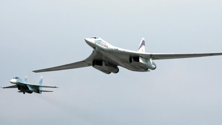 Un caza Su-27 (izquierda) y un bombardero estratégico Tu-160 (derecha) realizan un vuelo de práctica el Día de la Fuerza Aérea de Rusia