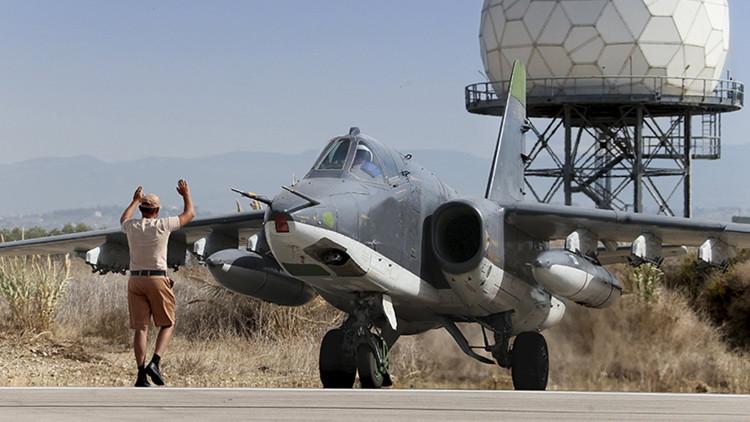 Un hombre hace señales al piloto de un Su-25 en la base aérea de Jmeimim cerca de la ciudad de Latakia