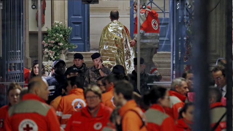 Las personas se calientan bajo mantas térmicas en una calle cercana a la sala de conciertos Bataclan de París después de los ataques terroristas.