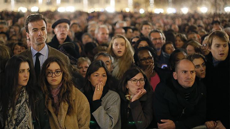 Gente reunida fuera de la catedral de Notre Dame, donde se celebra una misa por las víctimas de los atentados de París, 15 de noviembre de 2015