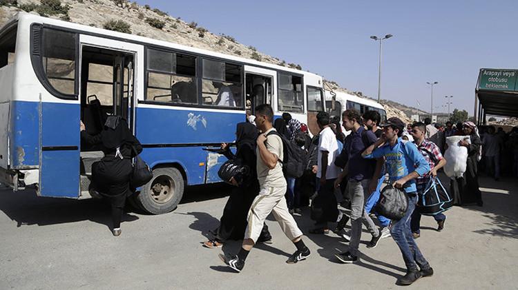Sirios se apresuran a subir al autobús para cruzar la frontera entre Siria y Turquía