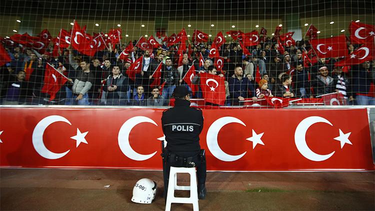 Un policía frente a aficionados turcos durante el partido amistoso de fútbol contra Grecia en el estadio Basaksehir Fatih Terim de Estambul el 17 de noviembre de 2015.
