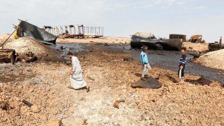 Civiles observan los daños en una refinería que fue blanco de los ataques de los aviones de EE.UU. cerca de la ciudad siria de Raqqa