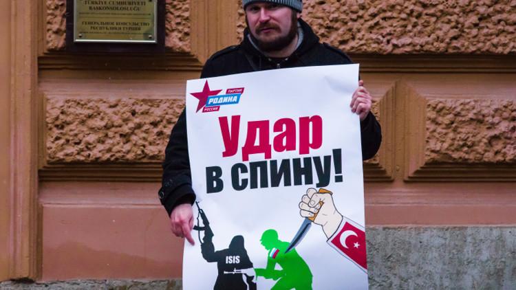 Un manifestante ruso sostiene un cartel que reza 'Puñalada por la espalda', en San Petersburgo
