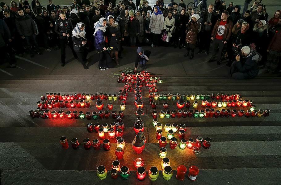 La gente pone flores junto una cruz hecha con 224 velas en las escaleras de la Catedral de Cristo Salvador en Moscú.