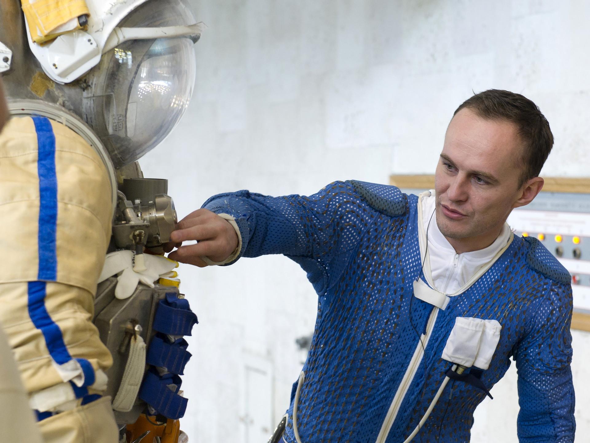 El cosmonauta ruso Serguéi Riazánskiy inspecciona su traje espacial antes de un ejercicio de entrenamiento en el centro de entrenamiento de cosmonautas Star City en las afueras de Moscú.