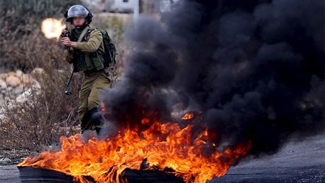 Soldado israelí dispara un arma contra manifestantes palestinos cerca de Cisjordana, 30 de octubre 2015