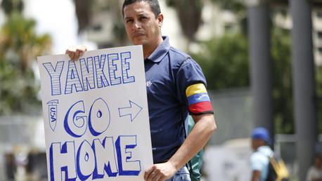 """Partidario del presidente venezolano, Nicolás Maduro, sostiene un cartel que reza """"Yankees go home"""" durante una manifestación contra el imperialismo en Caracas el 12 de marzo de 2015."""