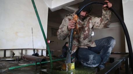 Un rebelde vierte combustible en un tanque en una refinería de Alepo