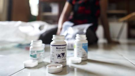 Un migrante infectado de VIH demuestra sus medicamentos durante una entrevista