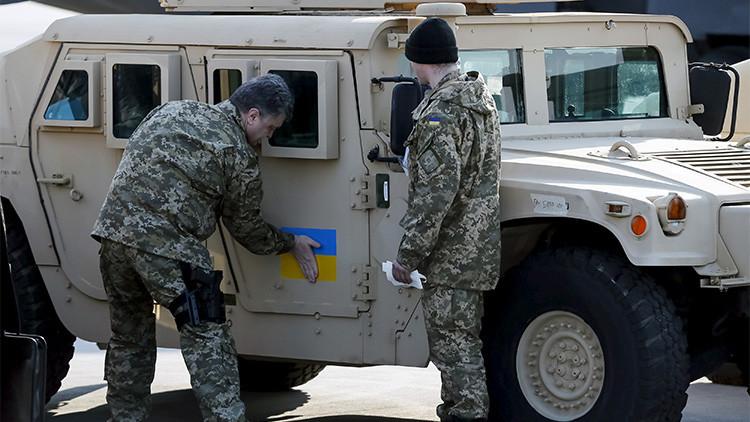 El presidente ucraniano, Piotr Poroshenko, pega una bandera nacional en uno de los vehículos entregados por EE.UU.